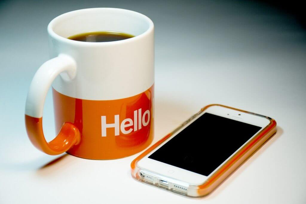 White and orange coffee cup featuring the word Hello next to a smartphone with an orange case